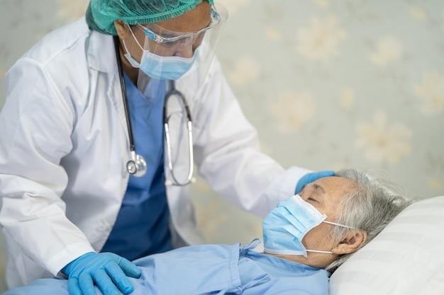 フェイスシールドとppeを身に着けているアジアの医師は、患者が安全感染を保護することを確認するためにニューノーマルに適合