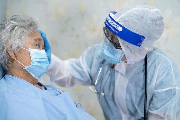 フェイスシールドとppeを身に着けているアジアの医師は、covid19コロナウイルスを保護するために新しい通常のスーツを着ています
