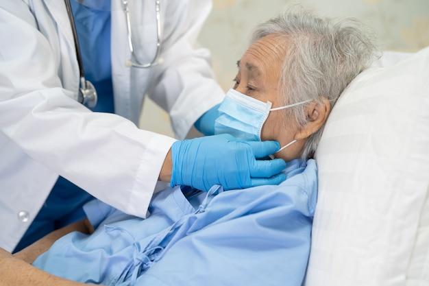 Covid19コロナウイルスを保護するためにフェイスシールドとppeスーツを着たアジアの医師