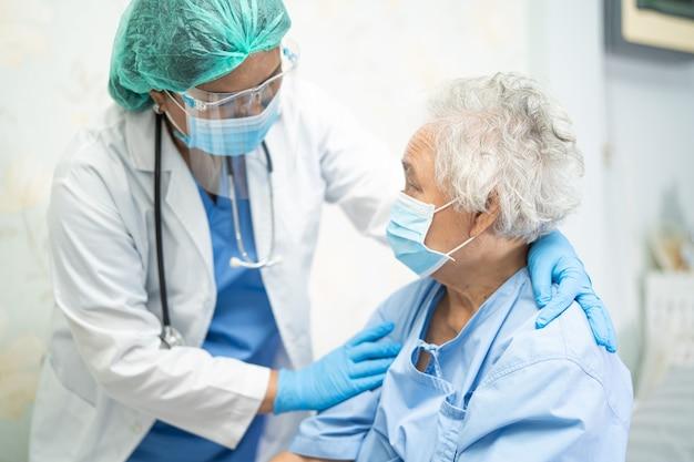 フェイスシールドとppeスーツを着て患者が安全感染を保護することを確認するアジアの医師covid19コロナウイルス