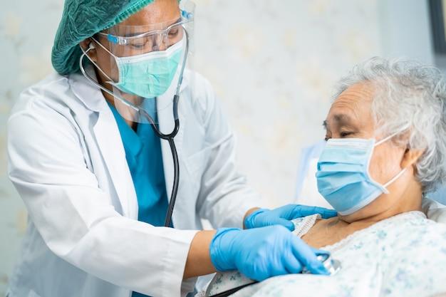 Covid-19コロナウイルスを保護するために顔面シールドとppeスーツを身に着けているアジアの医師。