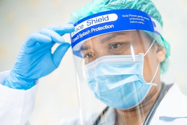 Covid-19コロナウイルスを保護するためにフェイスシールドとppeスーツを着たアジアの医師。
