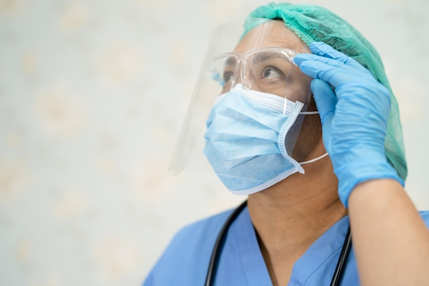 Asian doctor wearing face shield and ppe suit new normal to check patient protect coronavirus