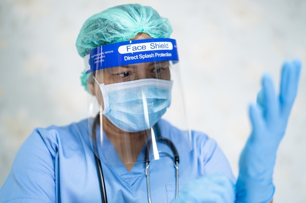 Asian doctor wearing face shield and ppe suit for protect covid-19 coronavirus.