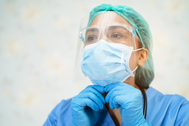 Asian doctor wearing face shield and ppe suit to protect covid-19 coronavirus.