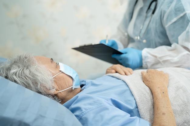 患者がcovid19コロナウイルスを保護することを確認するためにppeスーツを着たアジアの医師