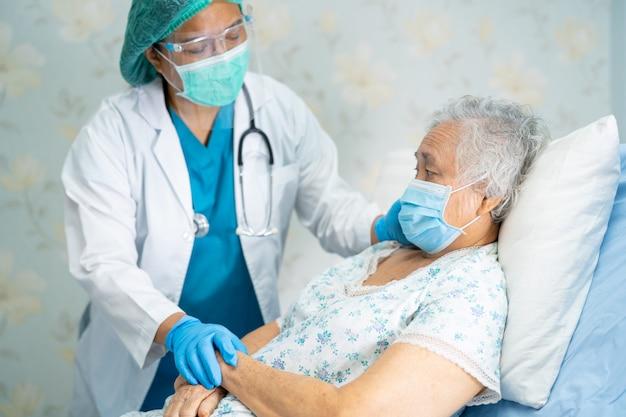 Ppeスーツを着て患者をチェックするアジアの医師