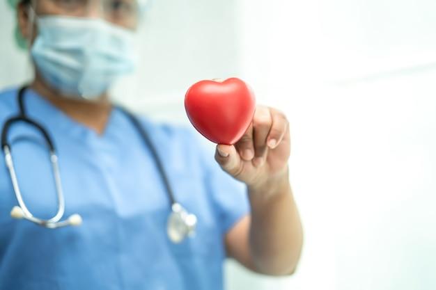 赤いハートを保持しているcovid19コロナウイルスを保護するためにppeスーツを着ているアジアの医師