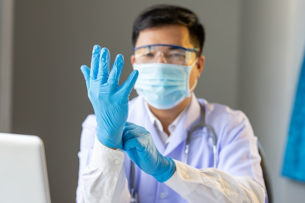 Asian doctor wearing protection glove for fighting covid-19 (corona virus)