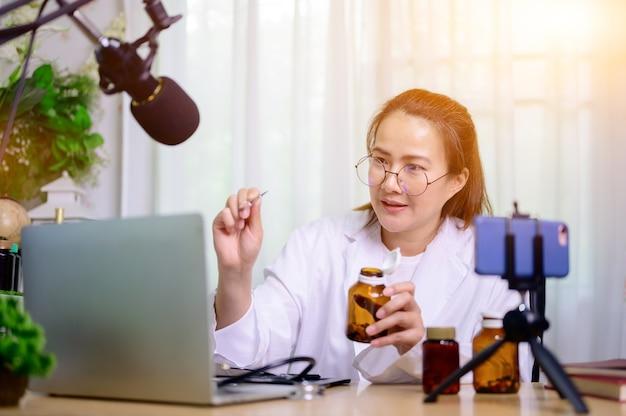 집에서 온라인으로 일하는 아시아 의사 여성. 약 복용 및 건강 관리를 위한 블로그 비디오 녹화.