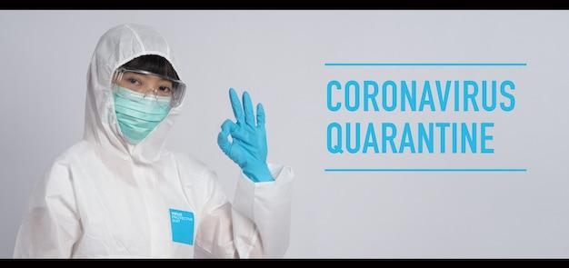 アジアの医師の女性は、ppeスーツまたは個人用保護具と医療用マスクと手袋を着用します