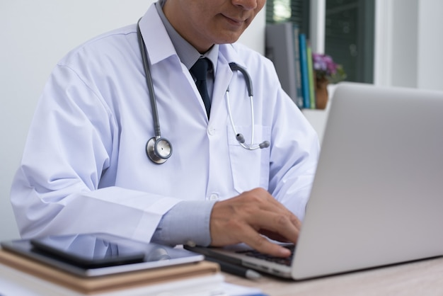Asian doctor working on laptop computer at doctor office electronics health records system emrs electronics medical records system concept