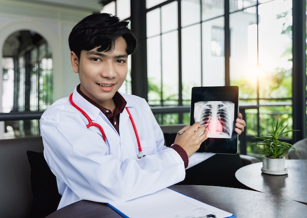 Asian doctors are using tablets to explain about body disorders via video call. a new normal of medical can treat follow up illnesses and consult remote patients in online  medical and remote concept