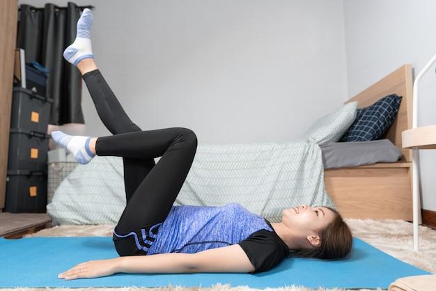 Азиатка занимается домашним фитнесом и занимается йогой на фитнес-коврике, делая упражнения