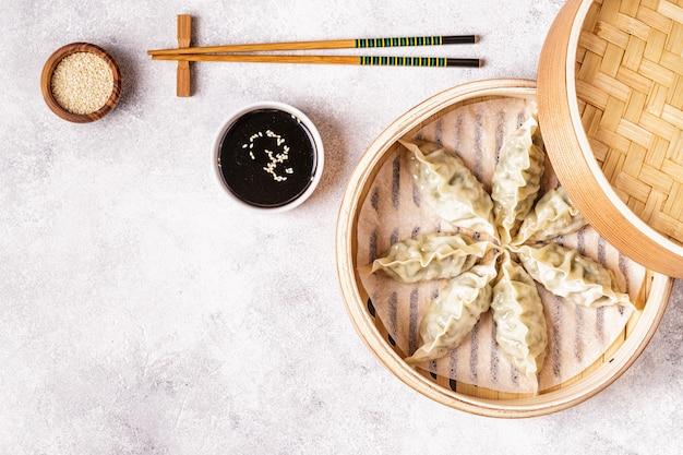 Asian dumplings, soy sauce, chopsticks, top view