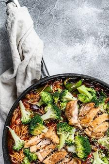 Азиатская яичная лапша с овощами и мясом на сковороде. серый фон вид сверху. пространство для текста