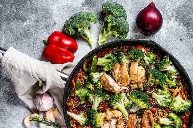 Азиатская яичная лапша с овощами и мясом на сковороде. вид сверху