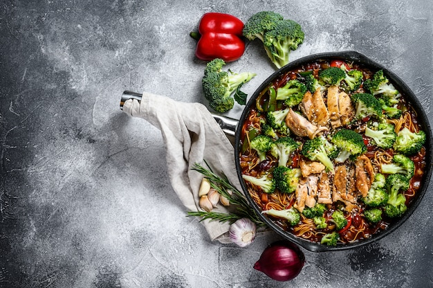 Asian egg noodles with vegetables and meat on cooking pan. top view.