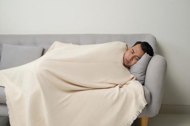 アジアの老人病人が自宅のソファに横たわって頭痛を感じる