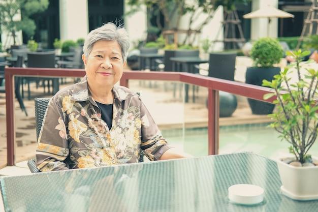 ホテルリゾートのバルコニーテラスでリラックスして休んでいるアジアの年配の女性女性