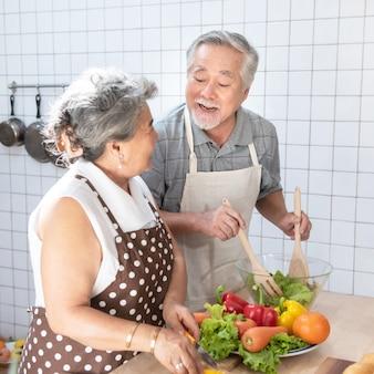 Asian elder senior couple cook in kitchen at home.