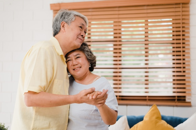 Asian elderly couple dancing together while listen to music in living room at home, sweet couple enjoy love moment while having fun when relaxed at home.