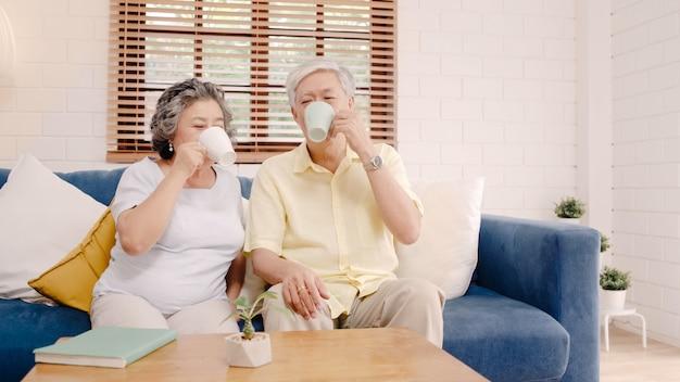 따뜻한 커피를 마시고 집에서 거실에서 함께 이야기하는 아시아 노인 부부는 집에서 편안하게 소파에 누워있는 동안 사랑의 순간을 즐길 수 있습니다.