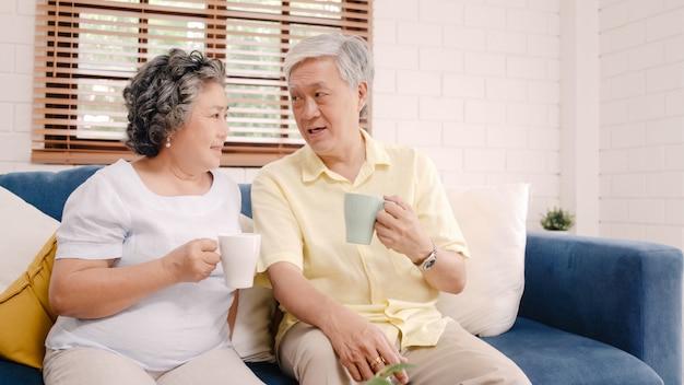 アジアの老夫婦が暖かいコーヒーを飲みながら自宅の居間で話していると、カップルは自宅でリラックスしたときソファの上に横たわっている間愛の瞬間を楽しんでいます。