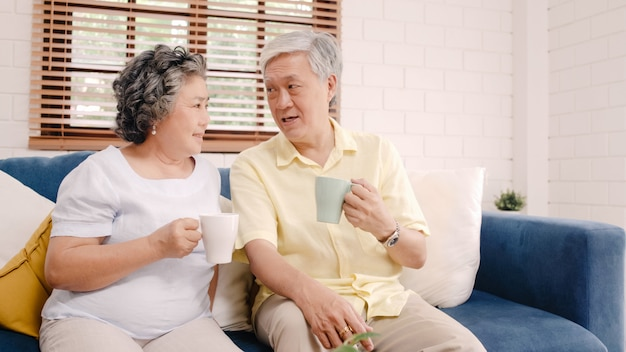 Asian elderly couple drinking warm coffee and talking together in living room at home, couple enjoy love moment while lying on sofa when relaxed at home.