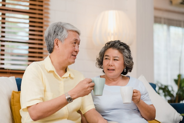 Asian elderly couple drinking warm coffee and talking together in living room at home, couple enjoy love moment while lying on sofa when relaxed at home. Free Photo