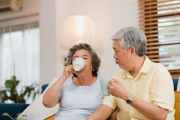 Asian elderly couple drinking warm coffee and talking together in living room at home, couple enjoy love moment while lying on sofa when relaxed at home