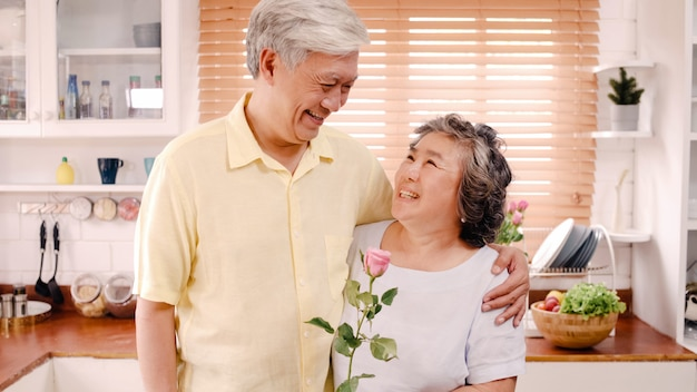 Asian elderly couple feeling happy smiling and holding flower and looking to camera while relax in kitchen at home. lifestyle senior family enjoy time at home concept. portrait looking at camera.