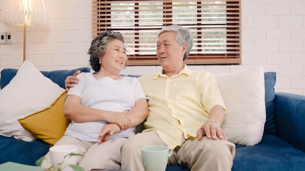Asian elderly couple feeling happy smiling and looking to camera while relax on the sofa in living room at home.