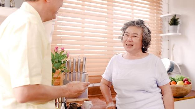 アジアの老夫婦が自宅の台所で朝食をとります。中国の甘いカップルの男が自宅で彼の妻にクッキーを食べます。