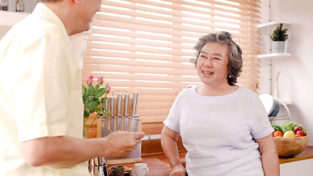 Asian elderly couple having breakfast in the kitchen at home. chinese sweet couple man feeding cookies to his wife at home.
