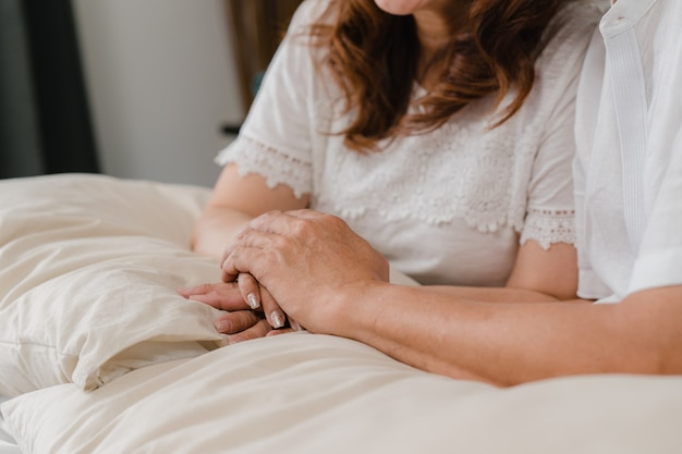 Asian elderly couple holding their hands while taking together in bedroom, couple feeling happy share and support each other lying on bed at home. lifestyle senior family at home concept.