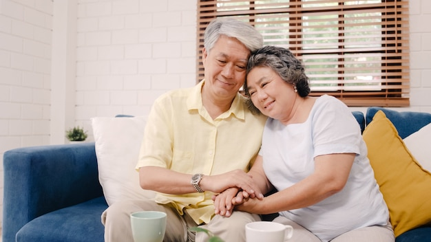 Asian elderly couple holding their hands while taking together in living room, couple feeling happy share and support each other lying on sofa at home.