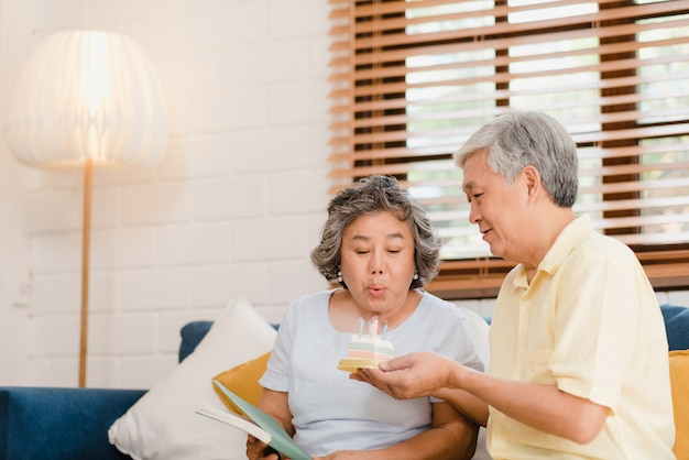 Asian elderly couple man holding cake celebrating wife's birthday in living room at home. japanese couple enjoy love moment together at home.