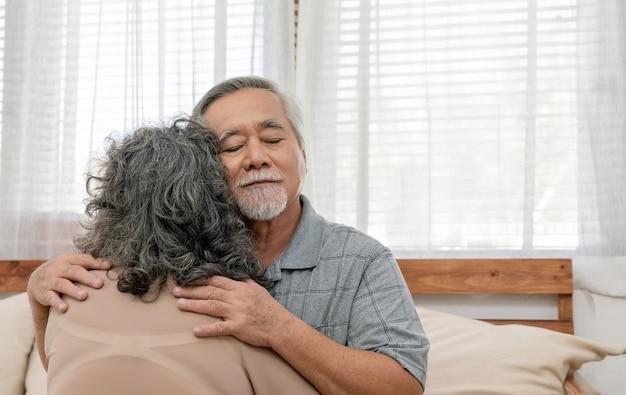 아시아 노인 부부는 집 거실에 있는 소파에 앉아 사랑과 보살핌을 받으며 행복한 은퇴 생활을 하고 있습니다.