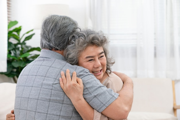 Asian elderly couple retirement happy embrace each other while sitting on the sofa in the living room at home with love and care.