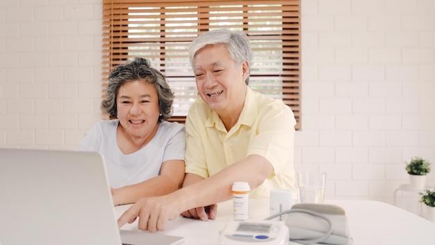 Азиатские пожилые пары используя конференцию компьтер-книжки с доктором о данных по медицины в живущей комнате, парах используя время совместно пока лежащ на софе дома.