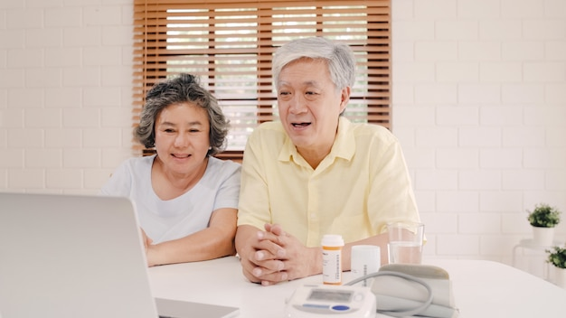 Asian elderly couple using laptop conference with doctor about medicine information in living room, couple using time together while lying on sofa at home.