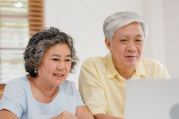Asian elderly couple using laptop conference with doctor about medicine information in living room