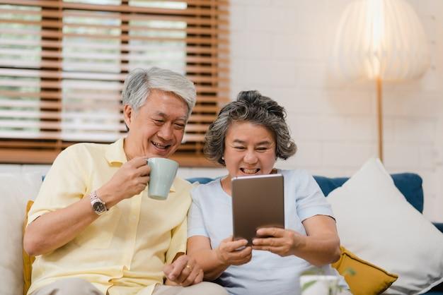 태블릿을 사용하고 집에서 거실에서 커피를 마시는 아시아 노인 부부, 몇 집에서 편안하게 소파에 누워있는 동안 사랑의 순간을 즐길 수 있습니다.