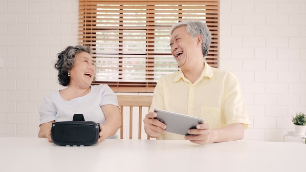 Asian elderly couple using tablet and virtual reality simulator playing games in living room, couple feeling happy using time together lying on table at home.