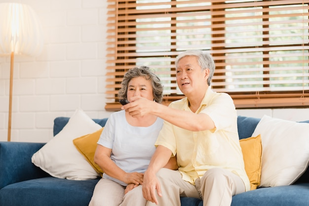 Asian elderly couple watching television in living room at home, sweet couple enjoy love moment while lying on the sofa when relaxed at home.