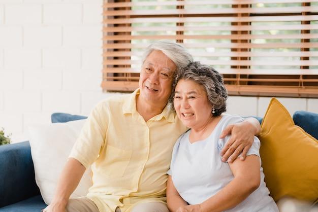 Le coppie anziane asiatiche che guardano la televisione in salone a casa, coppie dolci godono del momento di amore mentre si trovano sul sofà una volta rilassato a casa.