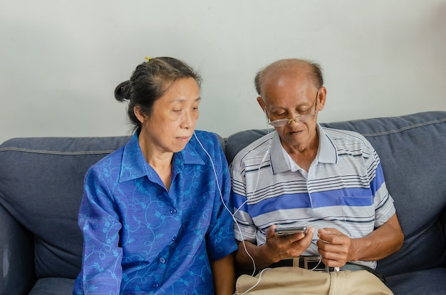 Asian elderly couples watch mobile phones and use headphones on the sofa