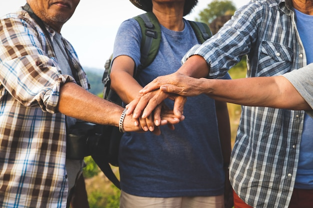 Азиатские пожилые группы путешествия, треккинг и горы они объединяются, счастливой жизни после выхода на пенсию.