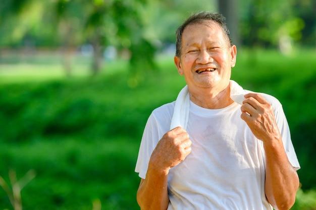 アジアの老人またはシニアランナージョギングで楽しく笑顔公園でのアウトドアやウォーキングトレーニング。